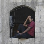 A Palestinian man looks at a neighboring house which police said was destroyed in Israeli air strikes in Khan Younis in the southern Gaza Strip