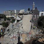 Palestinians stand next to a destroyed house following what police said was an Israeli air strike in central Gaza Strip