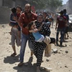 A Palestinian woman runs carrying a girl following what police said was an Israeli air strike on a house in Gaza city