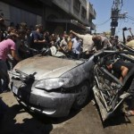 Palestinians gather around the remains of a car which police said was targeted in an Israeli air strike in Gaza City